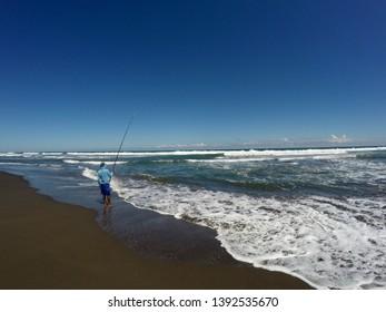 a man fishing on ketawang beach
