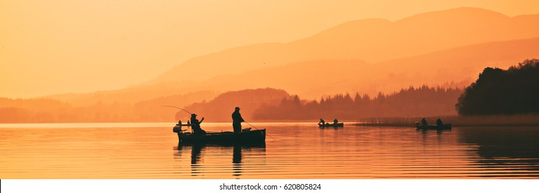 Man fishing on lake from boat at sunset. Lake of Menteith, Stirlingshire, Scotland, UK