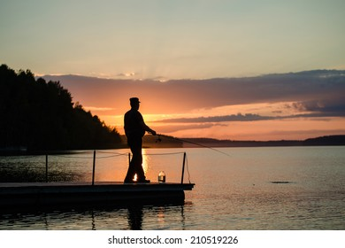 man fishing on a lake from the bridge at sunset