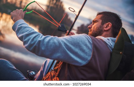 Man fishing on the river. Angler feeding fishes with slingshot. Sport, recreation, lifestyle