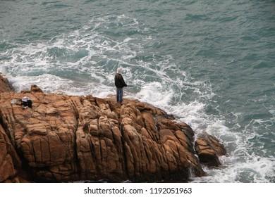 Man fishing on rocks with crashing waves