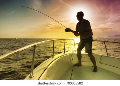 man fishing on the sea from the boat at sunset