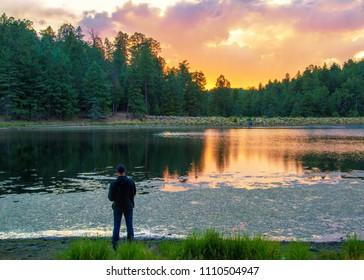 Man fishing on the shore of Riggs Flat lake on Mount Graham at sunset