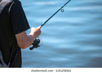 the man is fishing with a fishing rod, close up