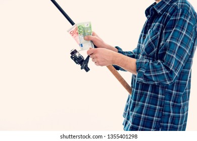man with fishing rod and money in blue plaid shirt in front of white background