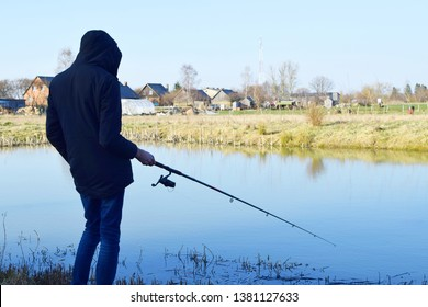Man fishing with fishing rod on pond in cold spring day. Hobbies, recreation and leisure outdoor activities  concept.