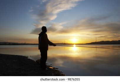 man with fishing rod on the sunset
