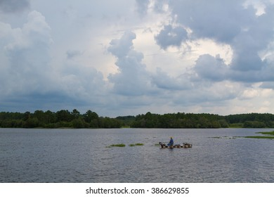 man fishing from small boat on deserted lake with menacing clouds on the horizon