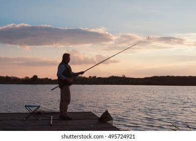man fishing in sunset on pond