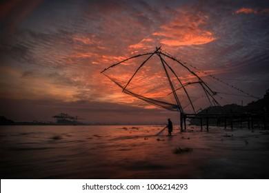 Man fishing under a chinese net  in kochi