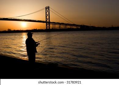 Man fishing with view of International Windsor, Ontario - Detroit, Michigan Border Crossing the Ambassador Bridge.