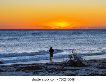 A man fishing in the waves on a Florida beach as the sun rises