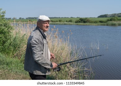 Man fishing while standing on pond bank