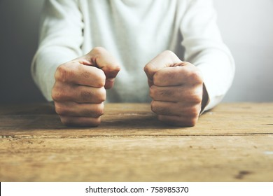 man fists clenched on a wooden table in anger