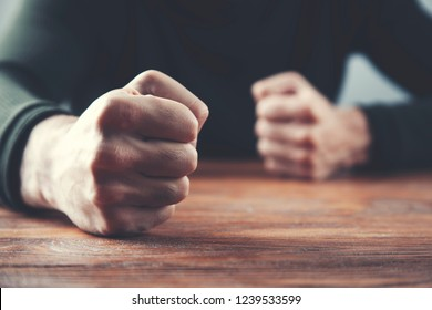 man fists on a wooden table