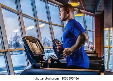 man fitnes in sportswear running on treadmill at gym