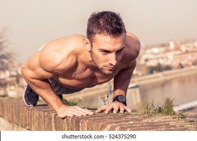 Man fitness model training pushups outdoors