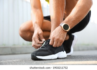 Man with fitness tracker tying shoelaces outdoors, closeup