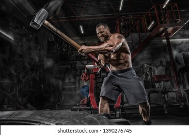 Man fitness training with large and heavy tire hits hammer. Concept workout, cross strength