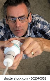Man fitting a low energy CFL light bulb to replace an old-fashioned tungsten incandescent light bulb