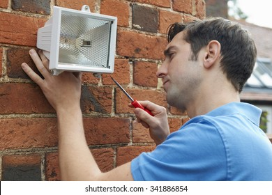 Man Fitting Security Light To Wall Of House