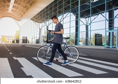 Man with a fixie bicycle walking on the road. young hipster with retro bicycle walking on the crosswalk and texting on the cellphone