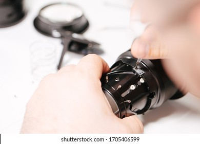 A man is fixing a camera lens with a screwdriver. Disassemble the digital technical device into parts and details. View from the top.