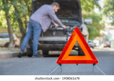 Man fixing car on road. Car Breakdown while driving. Driver looks on breakdown under the hood of car. Red triangular stop sign on road.