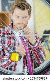 man fixing chainring on a bicycle workshop