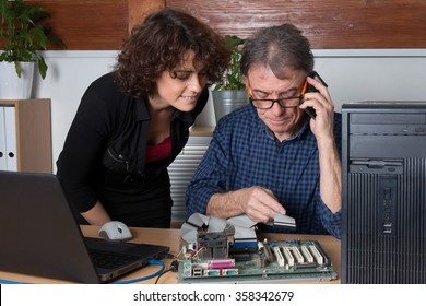 Man fixing a computer in front of female customer at office