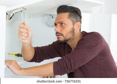 man fixing the cupboard door