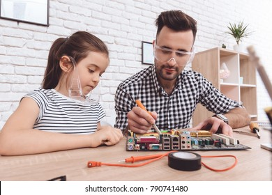 The man is fixing the motherboard. A little girl looks at how her father works. A repairman and his little daughter. A man is fixing a motherboard with a soldering iron.