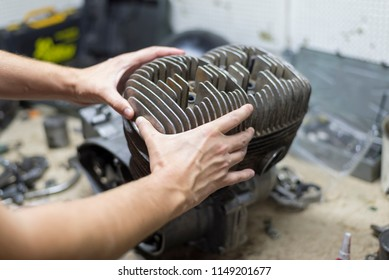 A man fixing a motorcycle motor in a garage,hands holding a cylinder, close-up