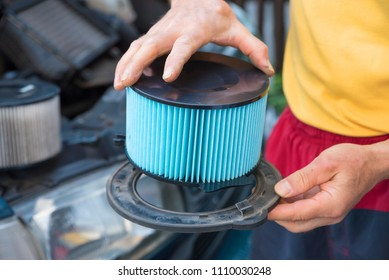 man fixing new air filter of the car in a holder. detail shot with selective focus.