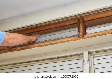Man fixing an old blind in its wooden box