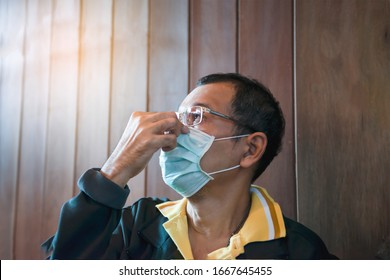 Man fixing on his surgical mask holding the nose mask for protect Covid-19 or PM 2.5 dust and serious of the air pollution indoor and wooden at home backgrround, Male in glasses, Surgical mask,