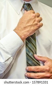 man fixing a tie with hands in white shirt