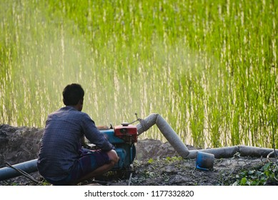 Man fixing a water machine sitting around an agricultural field unique photo