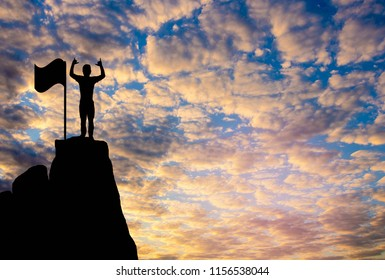 A man and  flag  Silhouette  photo. A man show hand and standing on cliff. A man happy and good feel  for nature. lifestyle , freedom  , He is see sun set. Photo concept  achievement and Silhouette.
