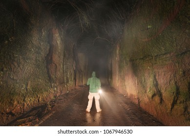 Man with a flashlight exploring in the dark forest