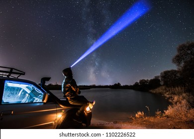 A man with flashlight looking uptsairs to the night sky and Milky Way. Some grain from high iso exists