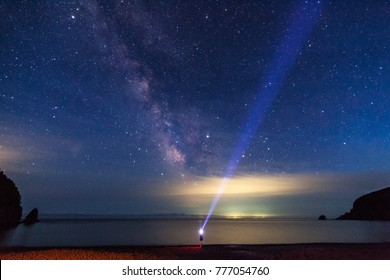 A man with flashlight looking uptsairs to the night sky and Milky Way