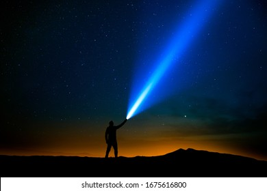 Man with flashlight pointed at the starry sky