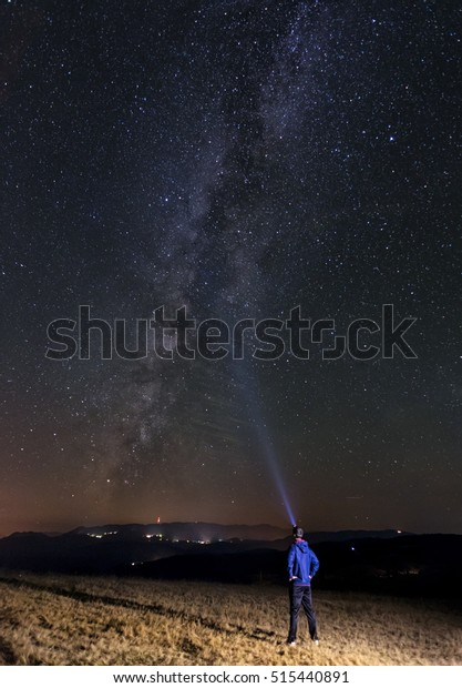 Man with a flashlight trying to light up the night sky and the milky way.