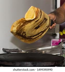 Man flipping pancake oven the pan