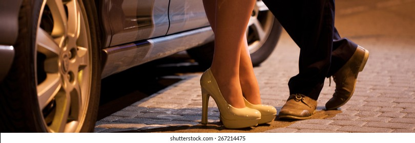 Man flirting with prostitute next to his car