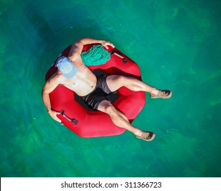 a man floating down a river in a blow up tube with a baseball cap on and shorts on a hot summer day from overhead