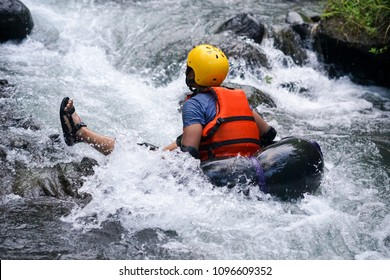 Man floating down a river stream in a blow up tube