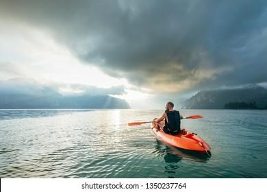 Man floating on kayak under sunrise sky on Cheow Lan Lake, Khao Sok national park, Thailand