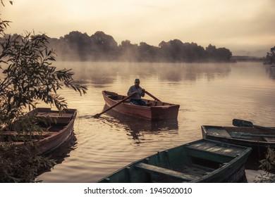 Homme flottant sur un bateau fluvial avec un beau paysage matinal à la campagne avec du brouillard sur la rivière avec de l'eau tranquille au lever du soleil